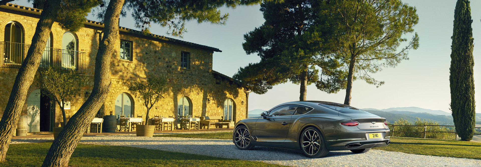 New-Continental-GT-2017-in-Tungsten-metallic-grey-colour-parked-by-a yellow-brick-building-in-the-countryside-surrounded-by-trees.